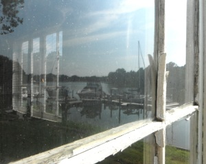 reflection of the docks and boats of the former Willard & Sons' Boatyard in the window of the sun room of the old house